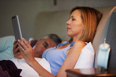 Couples âgés par milieu dans le lit avec la femme à l'aide de la tablette Image libre de droits