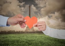 Couples hand holding heart against digitally generated eiffel tower at distance. Close-up of couples hand holding heart against digitally generated eiffel tower Stock Image