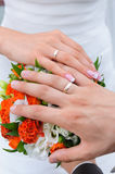 Couples hand with wedding rings. The bride and the groom showing their rings above the brides bouqet Royalty Free Stock Photos