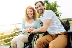 Couples handicapés joyeux se reposant en parc Images stock