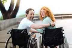 Couples handicapés positifs se reposant en parc Photo libre de droits