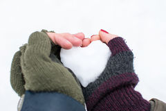 Couples hands holding heart shaped snowball Stock Photos