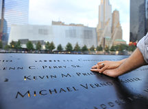 Couples hands laid on September 11 memorial. A shot of a person hand laid on the names in September 11 memorial Royalty Free Stock Photography