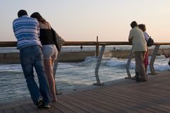 Couples in the harbor. Couples looking at the see at sunset Stock Photos