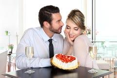 Couples heureux à la barre avec le vin mousseux et le gâteau, conce d'amour Images stock