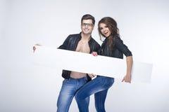 Couples heureux à la mode tenant le conseil blanc Image libre de droits