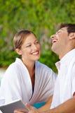 Couples heureux à la piscine avec l'ordinateur de comprimé Photos stock