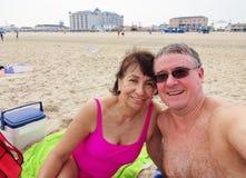 Couples heureux à la plage Photographie stock libre de droits