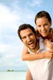 Couples heureux à la plage Photos libres de droits
