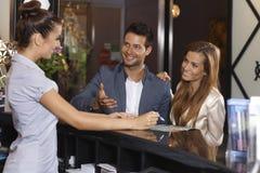 Couples heureux à la réception d'hôtel image libre de droits
