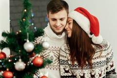 Couples heureux élégants décorant l'arbre de Noël émotion vraie d'amusement Photos libres de droits