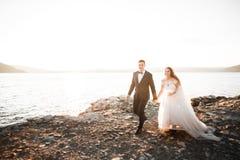 Couples heureux élégants élégants de mariage, jeune mariée, marié magnifique sur le fond de la mer et ciel Photos stock