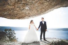 Couples heureux élégants élégants de mariage, jeune mariée, marié magnifique sur le fond de la mer et ciel Photo stock