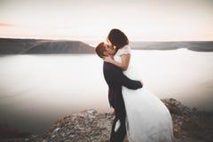 Couples heureux élégants élégants de mariage, jeune mariée, marié magnifique sur le fond de la mer et ciel Image stock