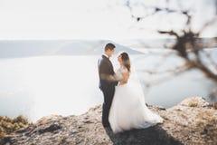 Couples heureux élégants élégants de mariage, jeune mariée, marié magnifique sur le fond de la mer et ciel Photographie stock