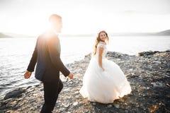 Couples heureux élégants élégants de mariage, jeune mariée, marié magnifique sur le fond de la mer et ciel Photos libres de droits