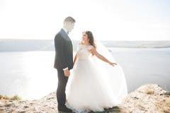 Couples heureux élégants élégants de mariage, jeune mariée, marié magnifique sur le fond de la mer et ciel Photo libre de droits