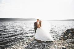 Couples heureux élégants élégants de mariage, jeune mariée, marié magnifique sur le fond de la mer et ciel Images stock