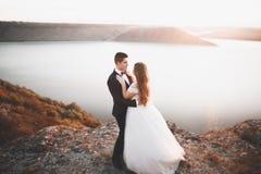 Couples heureux élégants élégants de mariage, jeune mariée, marié magnifique sur le fond de la mer et ciel Photographie stock libre de droits