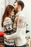 Couples heureux élégants embrassant sensuel à l'arbre de Noël joyeux Image libre de droits