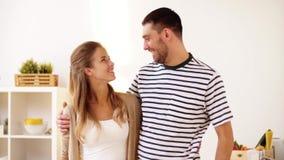 Couples heureux étreignant à la maison la cuisine banque de vidéos