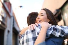 Couples heureux étreignant après s'être réuni dans la rue photographie stock