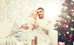 Couples heureux étreignant au-dessus de l'arbre de Noël Photographie stock libre de droits