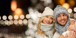 Couples heureux étreignant au-dessus des lumières de Noël Photo stock