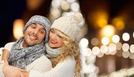 Couples heureux étreignant au-dessus des lumières de Noël Images libres de droits