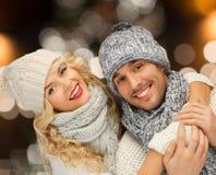 Couples heureux étreignant au-dessus des lumières de Noël Image stock