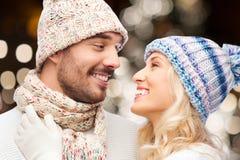 Couples heureux étreignant au-dessus des lumières de Noël Images stock