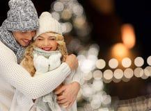 Couples heureux étreignant au-dessus des lumières de Noël Photos libres de droits