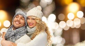 Couples heureux étreignant au-dessus des lumières de Noël Photos stock