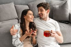 Couples heureux étreignant et regardant l'un l'autre tout en se reposant dessus Image stock