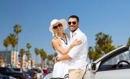 Couples heureux étreignant près de la voiture convertible Images libres de droits
