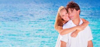 Couples heureux étreignant sur la plage Photos libres de droits