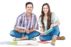 Couples heureux étudiant avec les livres et le comprimé tout en se reposant sur le plancher images libres de droits