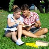 Couples heureux étudiant en parc Photos libres de droits
