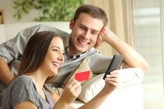Couples heureux achetant en ligne avec la carte de crédit Photos libres de droits