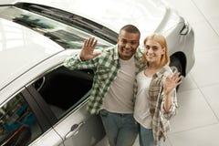 Couples heureux achetant la nouvelle voiture ensemble au concessionnaire photo stock