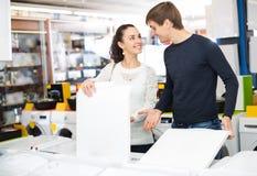 Couples heureux achetant le nouveau joint de vêtements dans le magasin d'électro-ménagers Images stock