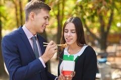 Couples heureux affectueux marchant en parc et mangeant les nouilles chinoises dans la boîte photo stock