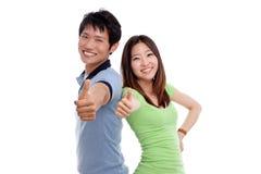 Couples heureux affichant des pouces. Image stock