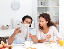 Couples heureux affichant le journal au déjeuner Photos libres de droits