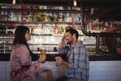 Couples heureux agissant l'un sur l'autre tout en ayant la bière au compteur Photo stock