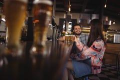 Couples heureux agissant l'un sur l'autre tout en ayant la bière au compteur Image libre de droits