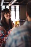Couples heureux agissant l'un sur l'autre tout en ayant la bière au compteur Image stock