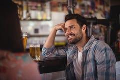Couples heureux agissant l'un sur l'autre tout en ayant la bière au compteur Photos stock