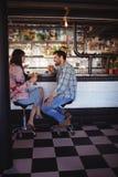 Couples heureux agissant l'un sur l'autre tout en ayant la bière au compteur Images stock