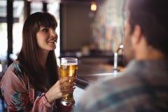 Couples heureux agissant l'un sur l'autre tout en ayant la bière au compteur Photo libre de droits